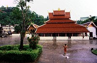 Laos, Luang Prabang, listed as World Heritage by UNESCO, Wat Maï Temple or Banpakham, the courtyard, novice running to shelter during a monsoon downpo...