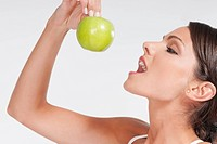 Close_up of a woman eating a granny smith apple