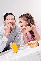 Man with his daughter having breakfast