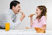 Man eating slices of bread with his daughter