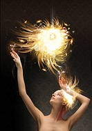 Woman reaching up to abstract glowing ball