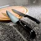 Two kitchen knives with a cutting board