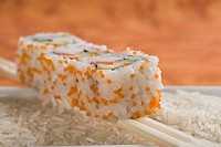 Close_up of uramaki sushi on chopsticks