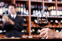 Man´s hand holding a wine glass in a bar