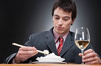 Close_up of a businessman eating rice with chopsticks