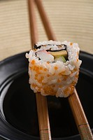 Close_up of a maki sushi with chopsticks on a bowl