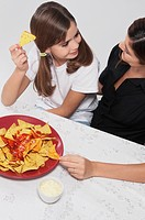Woman with her daughter eating nachos with salsa