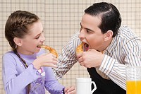 Close_up of man and his daughter eating croissants