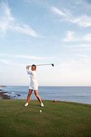 A woman playing golf by the sea Gran Canaria Spain.