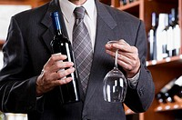 Businessman holding a wine bottle and a wine glass