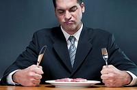 Businessman frowning at a raw steak