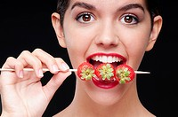 Close_up of a woman biting strawberries on a skewer