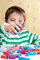 Close_up of a boy holding a handful of candies