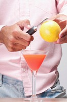 Mid section view of a man peeling a lemon over a cocktail