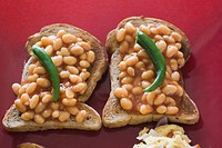 High angle view of baked beans on toasts with green chillies