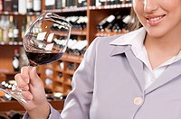 Businesswoman holding a glass of wine in a bar and smiling
