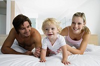 Young parents playing with baby 12_24 months on bed, baby crawling away