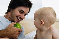 Young father playing with baby 6_12 months in bed, holding green apple