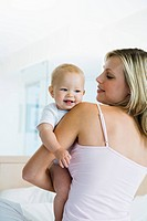 Young mother holding baby 6_12 months in bedroom, baby looking over shoulder
