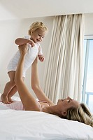 Young mother playing with baby 12_24 months on bed, holding up baby, smiling