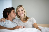 Young couple sitting on bed, smiling, hugging, drinking coffee