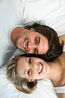 Young woman an man lying in bed, smiling, portrait