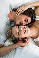 Young couple lying in bed, smiling, portrait from above (thumbnail)