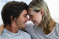 Young couple sitting on bed, smiling, looking in each others eyes, portrait (thumbnail)