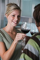 Young couple in modern kitchen toasting at each other with red wine