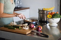 Young woman in kitchen, cooking pasta sauce, cutting board with vegetables (thumbnail)