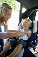 Young mother securing baby 12-24 months in car seat (thumbnail)