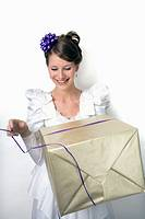 Young girl wears wedding dress and holds gift  Photographed in studio  She was 19 at the time of shoot and is of Irish ethnicity  Photographed July, 2...