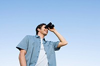 Man standing outdoors using binoculars (thumbnail)