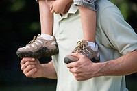 Father carrying son 4-7 on his shoulders, outdoors, close-up, detail (thumbnail)