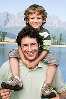Father carrying son 4_7 on his shoulders, outdoors, lake in background