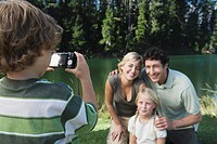 Boy photographing family outdoors, mother, father and sister posing for picture