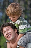 Father carrying son 4_7 on his shoulders, outdoors, forest in background