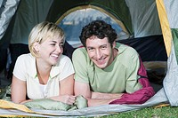 Young couple camping looking out of tent, laughing