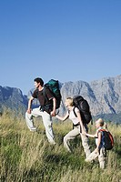 Young couple with daughter outdoors, hiking in mountains with backpack