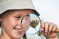 Girl 8_13 looking at flower through Magnifying glass, outdoors