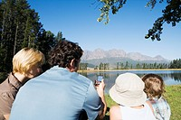 Young Family looking at compass, pointing at mountains, outdoors