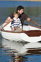 Father and son 4_7 rowing in rowing boat, on lake