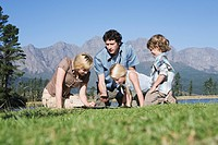 Young Family sitting on grass looking at map and compass, outdoors