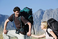 Young couple outdoors, hiking with backpack, mountains in background
