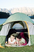 Young couple camping in tent, with lake and mountains in background