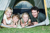 Young Family camping, looking out of tent, smiling