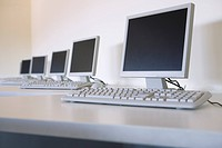 Row of computer monitors and keyboards in classroom