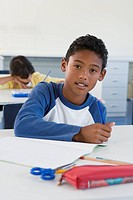 School boy 10_13 writing in classroom, looking at camera