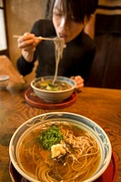 Woman eating noodles at traditional Japanese restaurant  Kyoto, Japan
