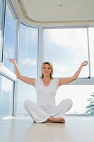 Senior woman sitting, doing Yoga exercise, indoors